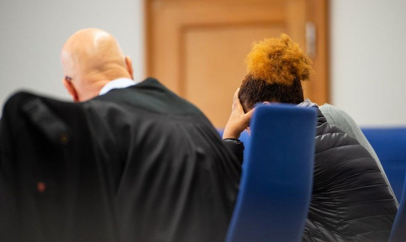 The accused sits before trial in addition to their defender in the district court Lüneburg.  - Philipp Schulze / dpa